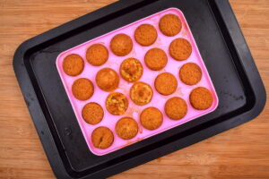 Cake balls in a pink cake pop mold on sheet pan, wooden background.