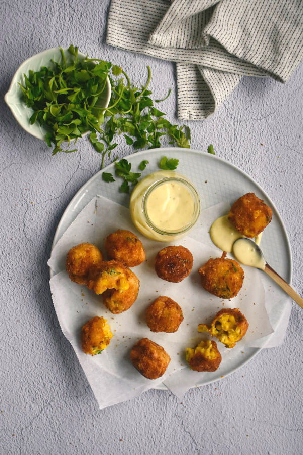 A plate of corn nuggets with dipping sauce, cilantro on the side.