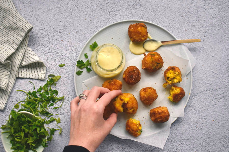 Corn nuggets on a plate with dipping sauce, cilantro on the side.