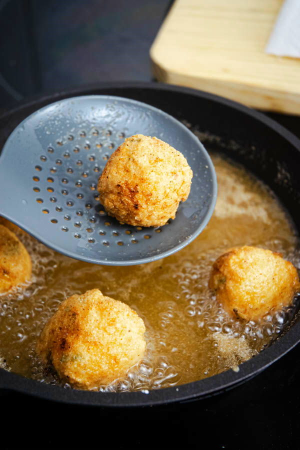 Fried corn nuggets in a pan with hot oil.