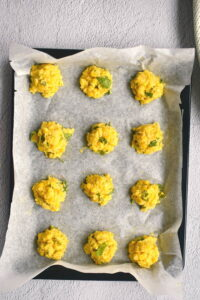 Frozen raw corn nuggets on a baking sheet with wax paper.