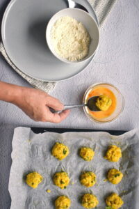 Raw corn nuggets on a wax paper lined baking sheet, bowls of egg and flour on the side.