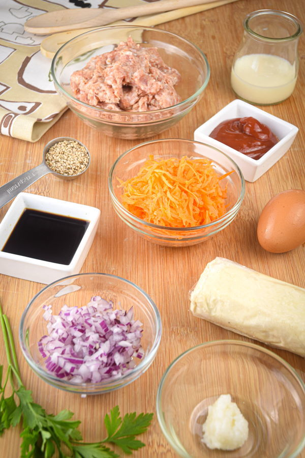 Sausage roll ingredients prepped on wooden background.