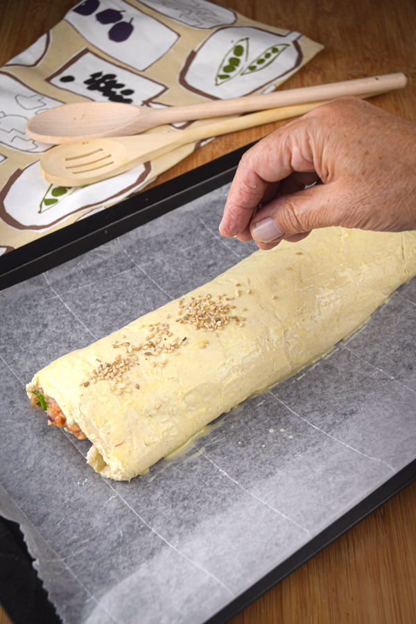 Raw sausage roll on a sheet pan.