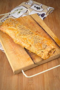 Sausage roll on a cutting board.