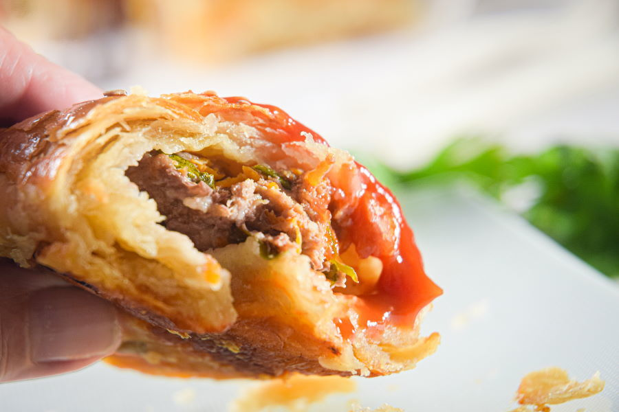 A sausage roll with sauce on it.