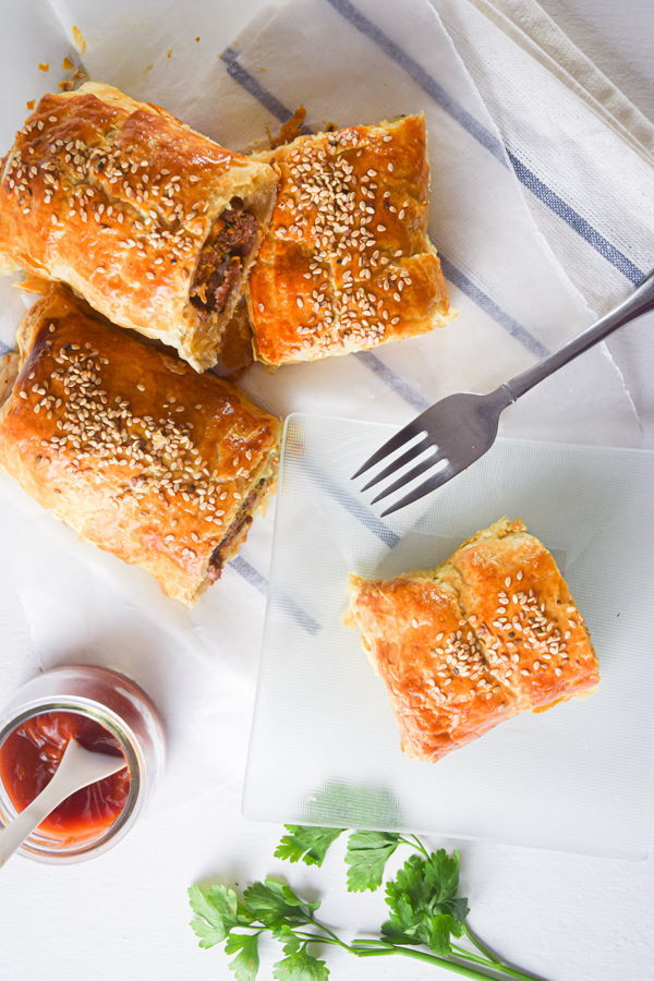 Sausage rolls on a plate with a fork and small jar of sauce on the side.