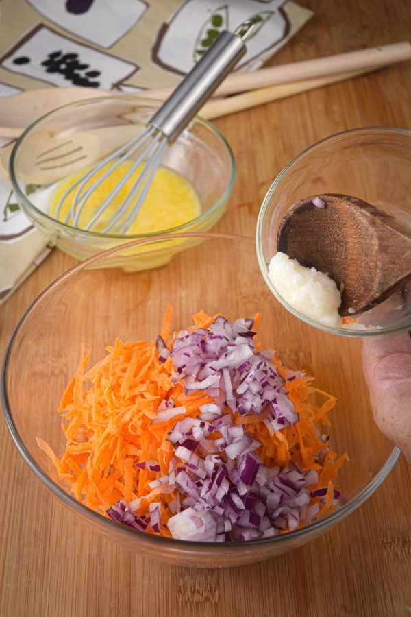 Ground sausage in a bowl with carrot, onion and garlic.