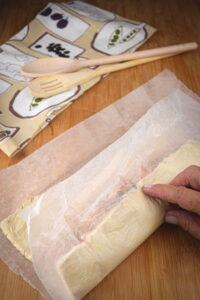 Raw sausage roll on parchment paper.