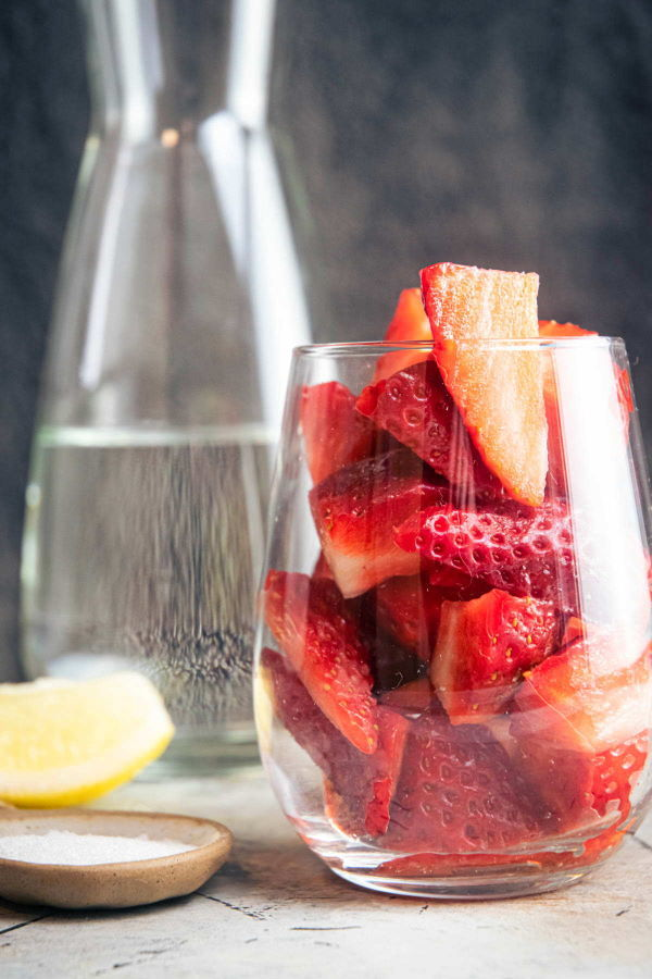 Quartered strawberries in a glass, water in a glass pitcher in the background.