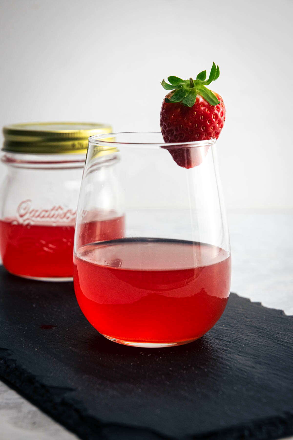 Strawberry liqueur in a jar and wine glass, fresh strawberry on the side.