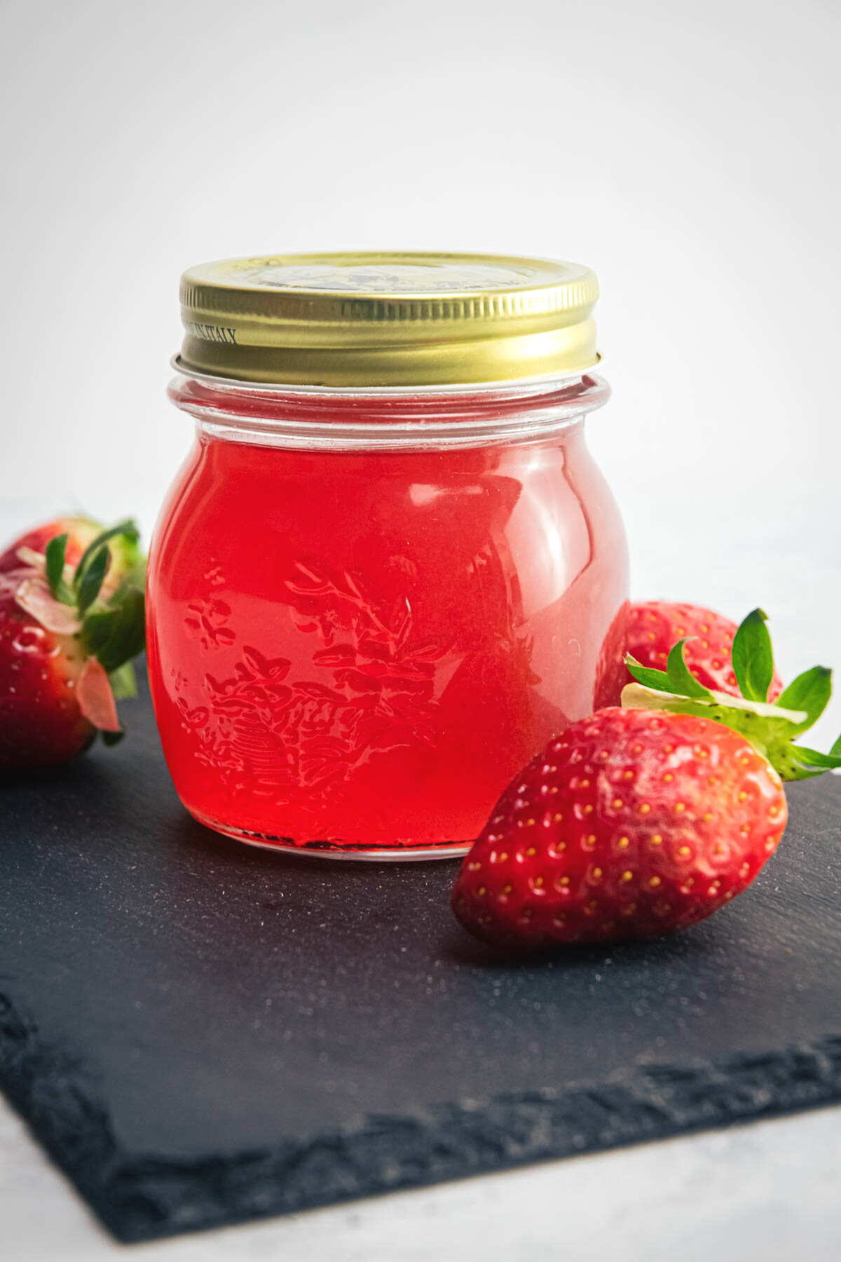 Strawberry liqueur in a jar, fresh strawberries on the side.