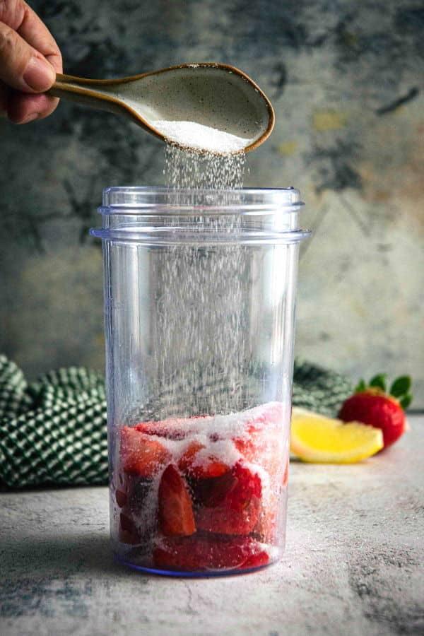 Strawberries and sugar in a blender jar.