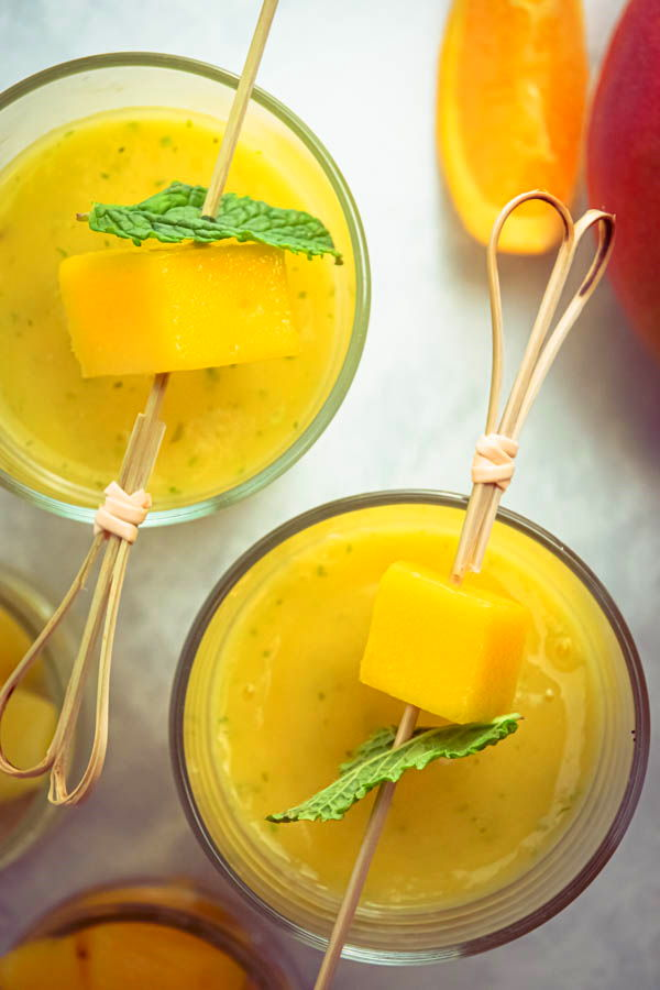 Mango pineapple smoothies in 2 glasses with mango and mint skewers.