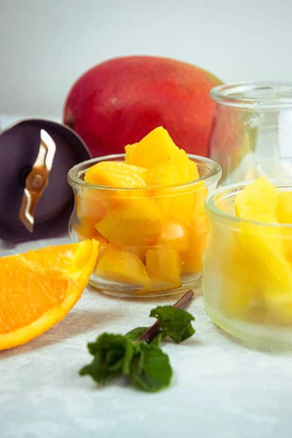 Mango pineapple smoothie ingredients on white background.