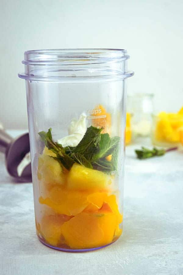 Mango pineapple smoothie ingredients in a jar.