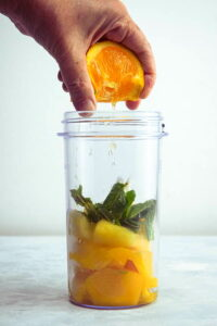 Mango pineapple smoothie ingredients in a jar with a freshly squeezed orange.