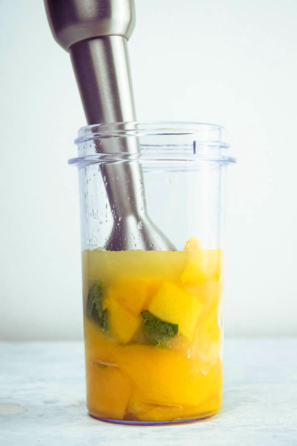 Mango pineapple smoothie and a blender, white background.