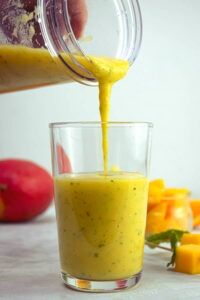 Mango pineapple smoothie being poured into a glass, fruit in the background.