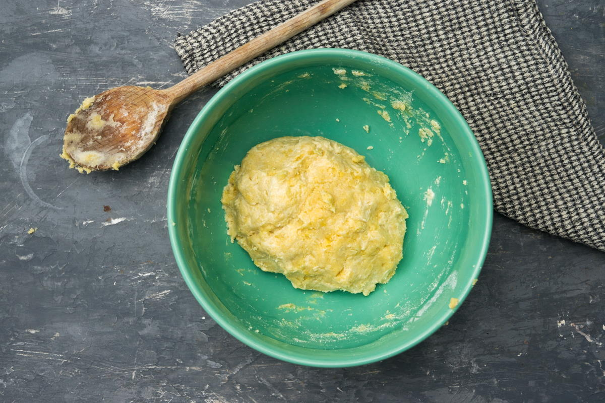 Galette pastry dough in a bowl, wooden spoon on the side.