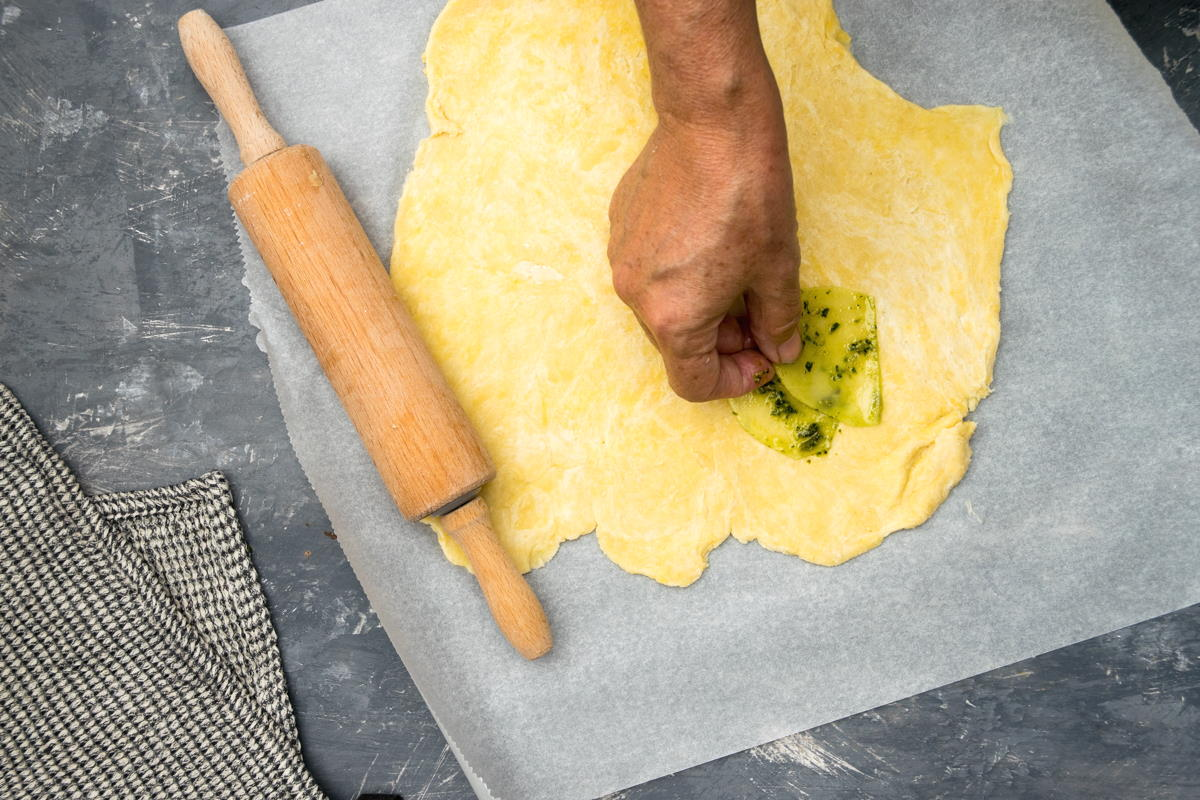 Pastry dough on parchment paper with a rolling pin and some potato slices.