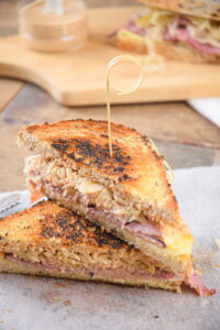 Reuben sandwich halves stacked on top of each other on wooden background.