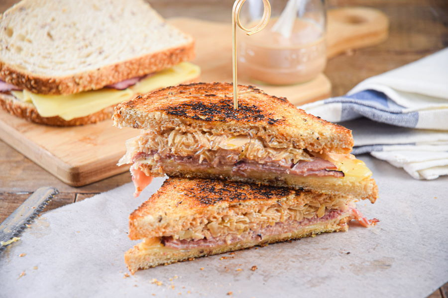Reuben sandwich halves stacked on top of each other on parchment.