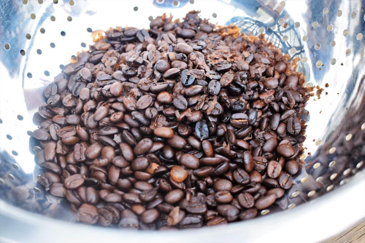 Coffee beans in metal colander.