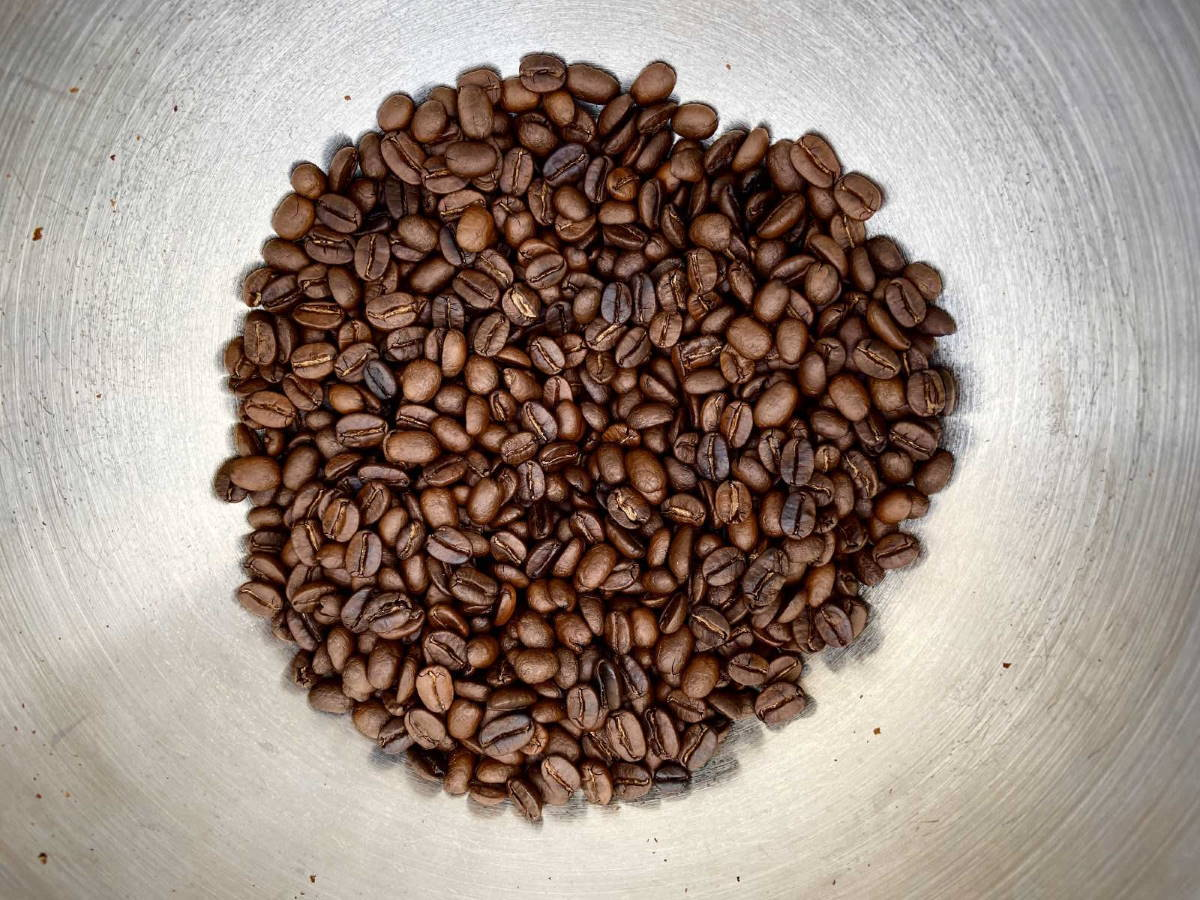 Coffee beans in metal bowl.