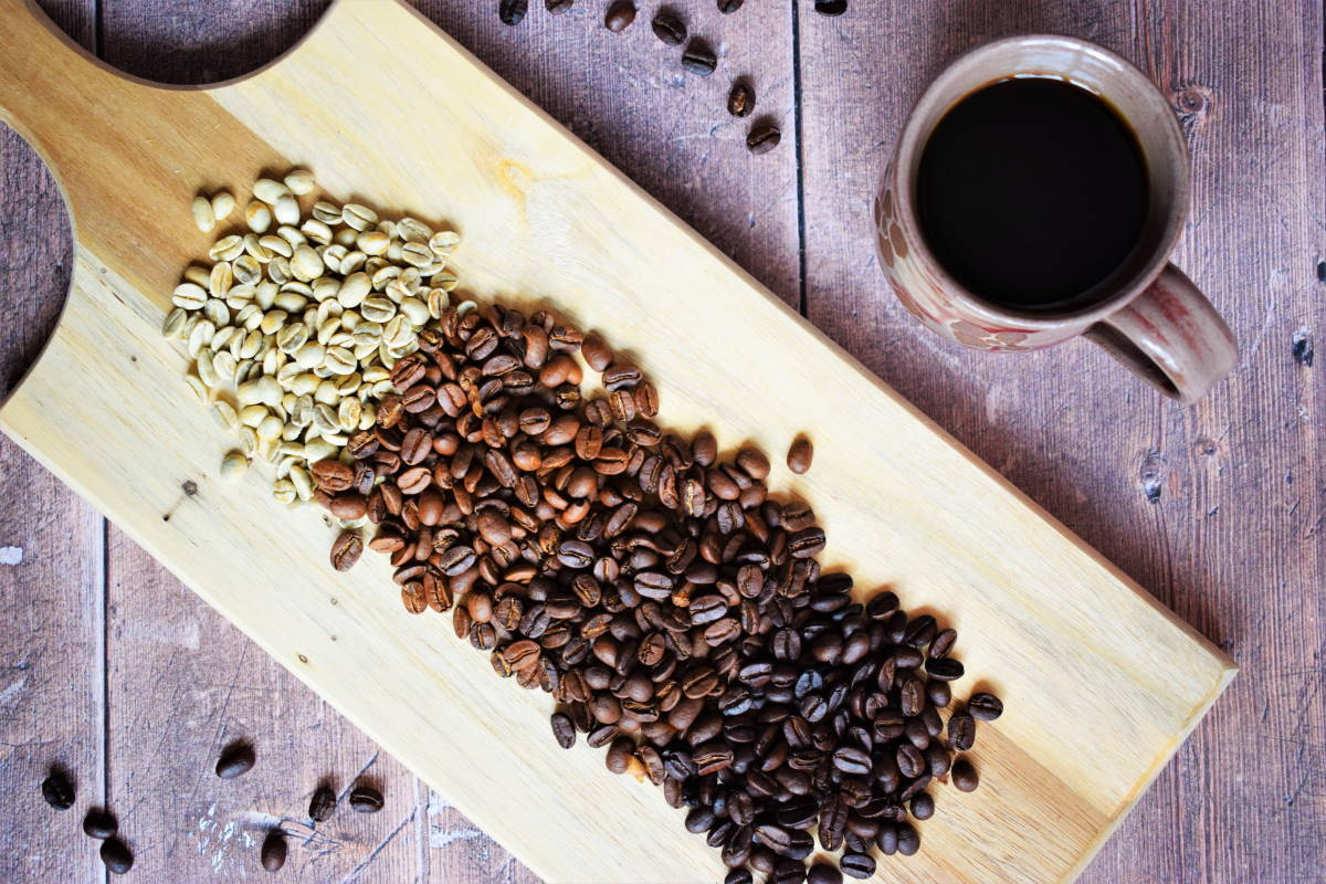 Green and brown coffee beans on wooden serving board, coffee mug on the side.