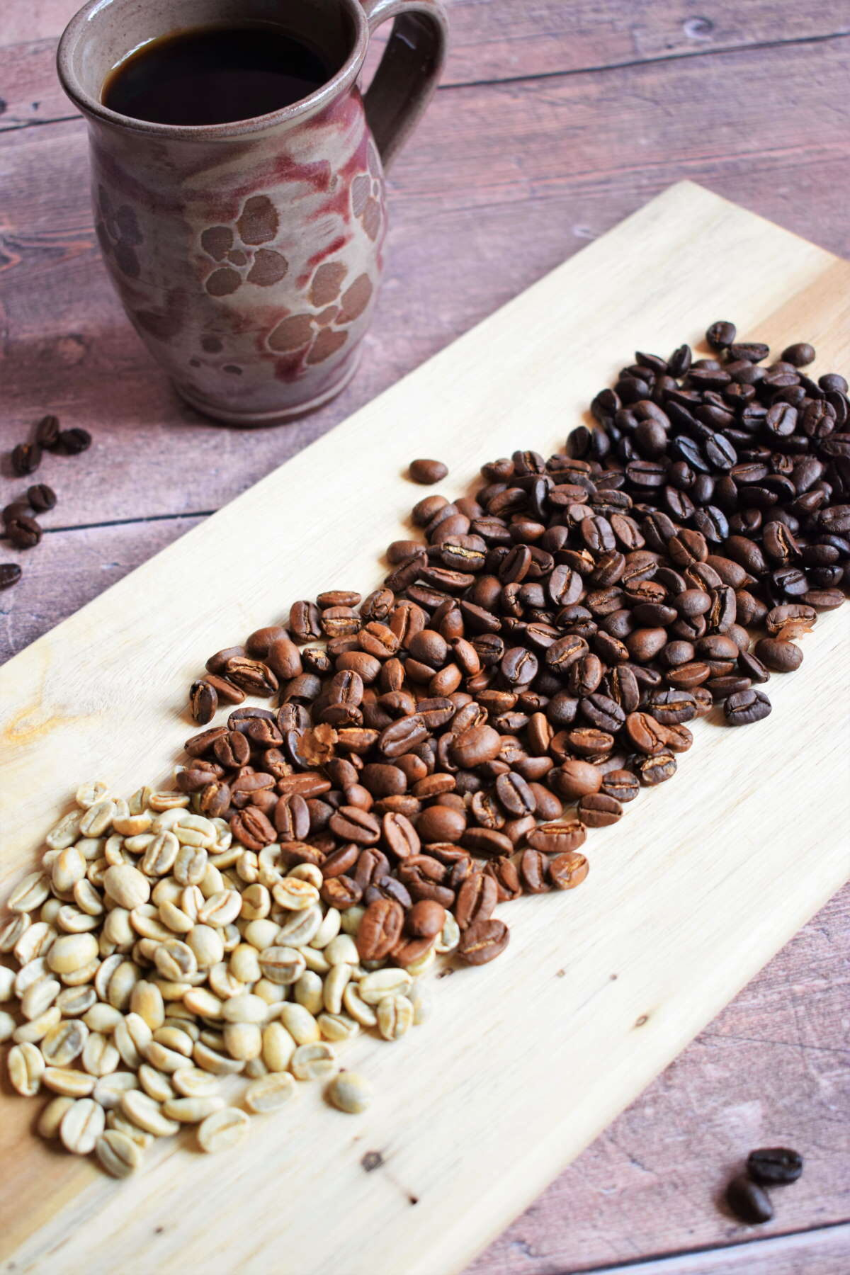 Green and brown coffee beans on wooden serving board, coffee mug in the background.