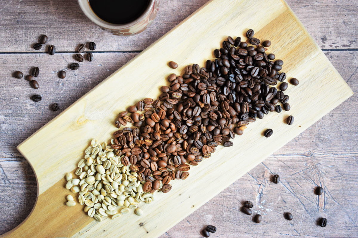 Green and brown coffee beans on wooden serving board.