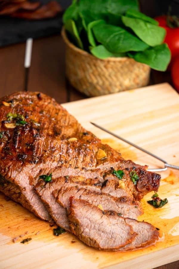 Grilled, sliced carne asada on wooden cutting board.