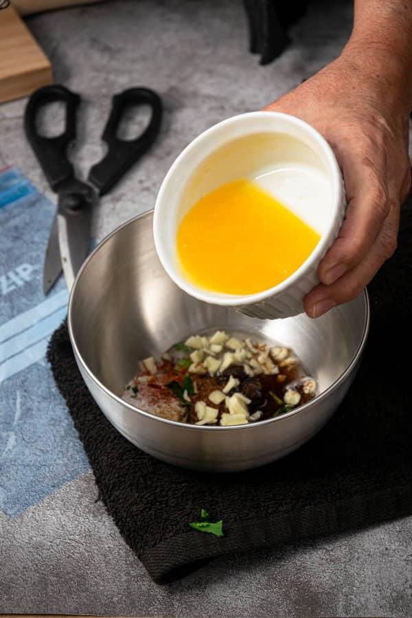 Carne asada marinade ingredients in metal bowl on black towel.