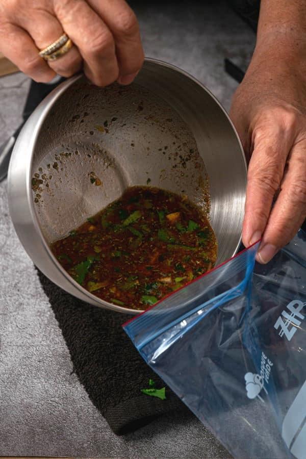 Carne asada marinade ingredients in metal bowl on black towel with a zip top bag.