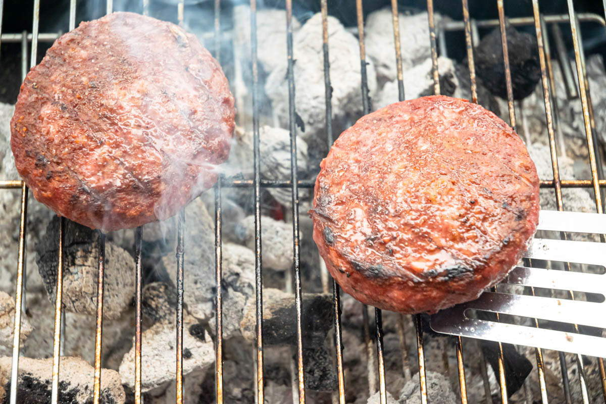 Burger patties on the charcoal grill.