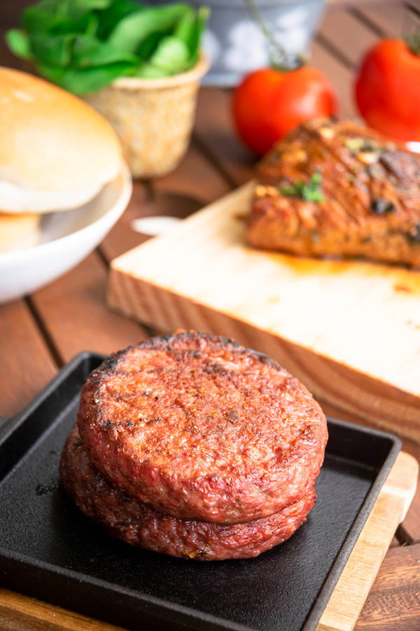 Cooked burger patties on a cast iron pan, on wooden table.