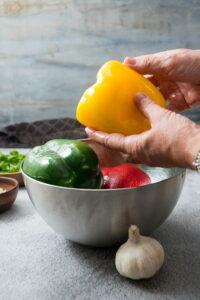 Bell peppers in a metal bowl, a head of garlic on the side.