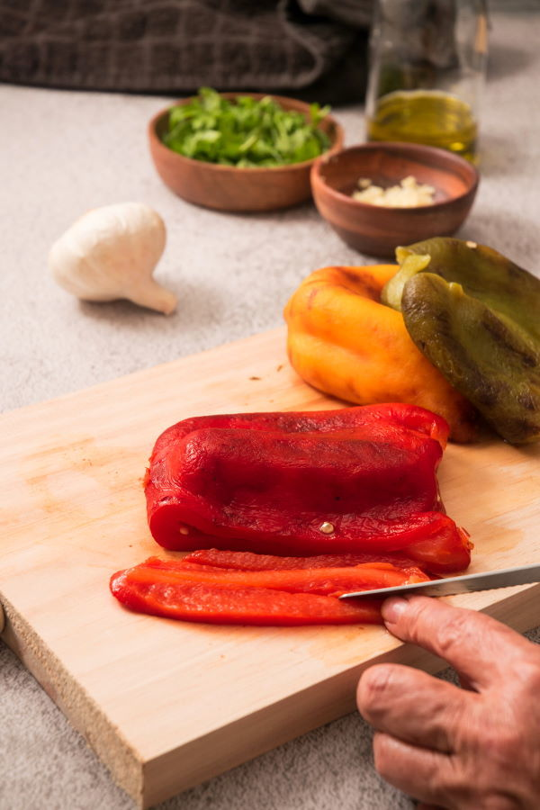 Grilled, skinned bell peppers on wooden board.