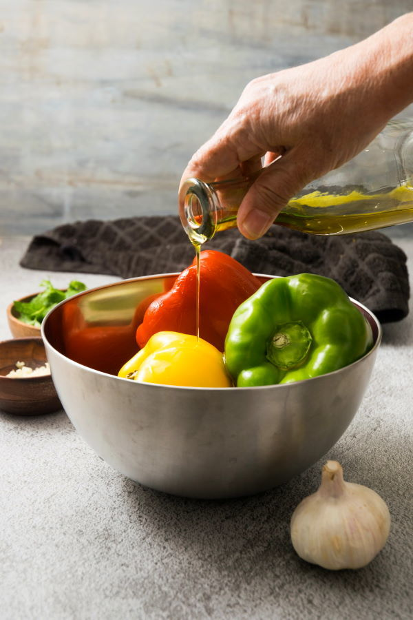 Bell peppers in a metal bowl with olive oil, a head of garlic on the side.