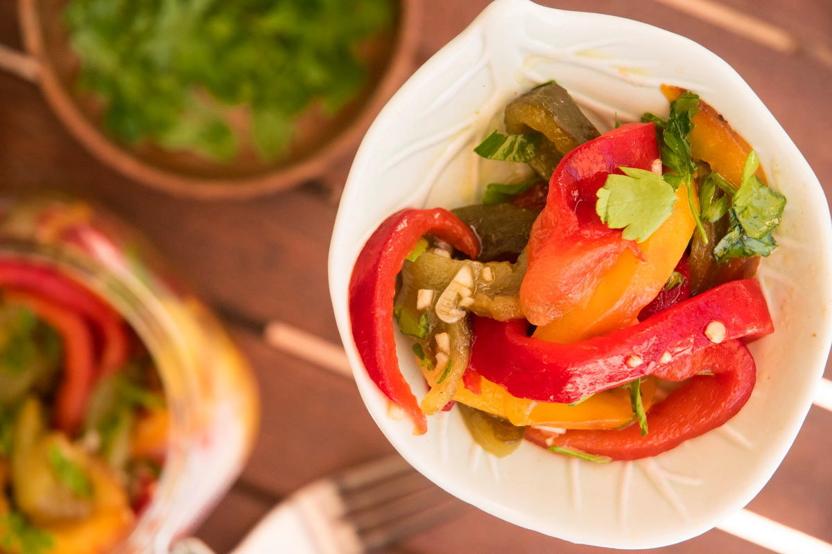 Grilled, sliced bell peppers in a bowl on wooden table.