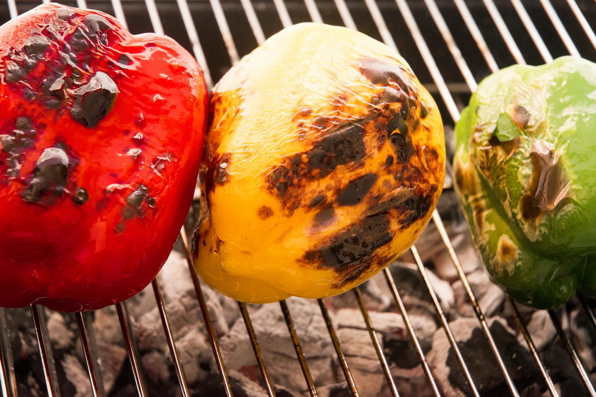 3 charred bell peppers on the grill.