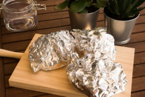 Foil wrapped bell peppers on a wooden board.