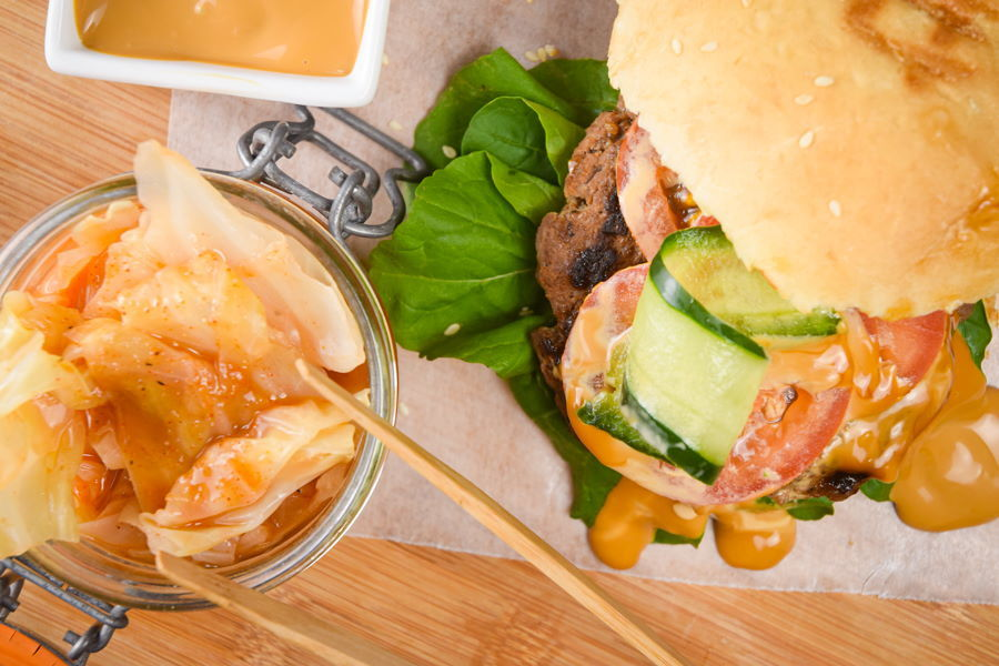 Kimchi burger with kimchi sauce on wooden background, sauce dish and a jar of kimchi on the side.