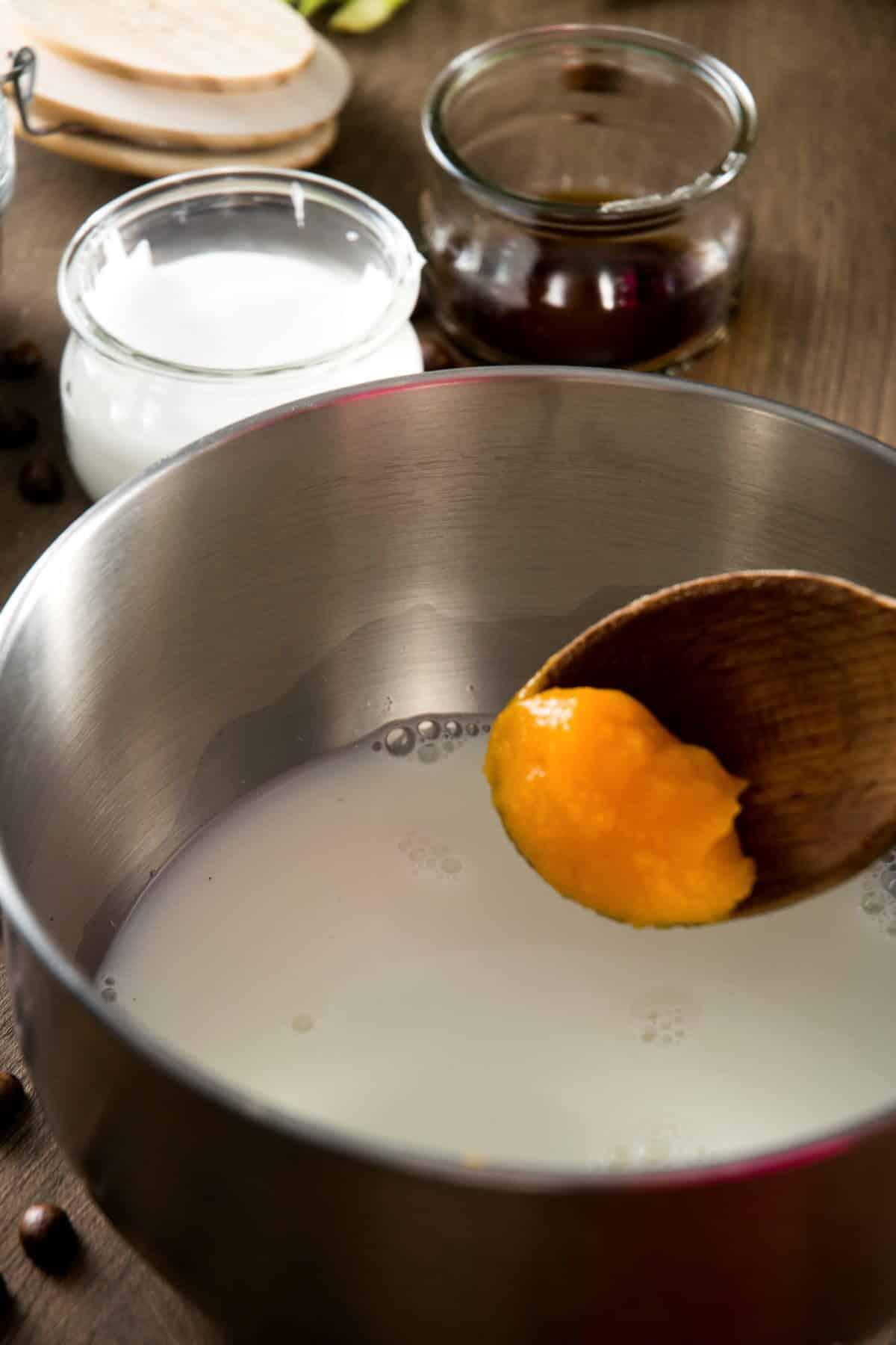 Pumpkin puree on a spoon and milk in a saucepan.