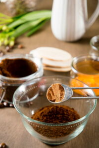 Pumpkin pie spice in a measuring spoon over a small bowl of coffee grind.