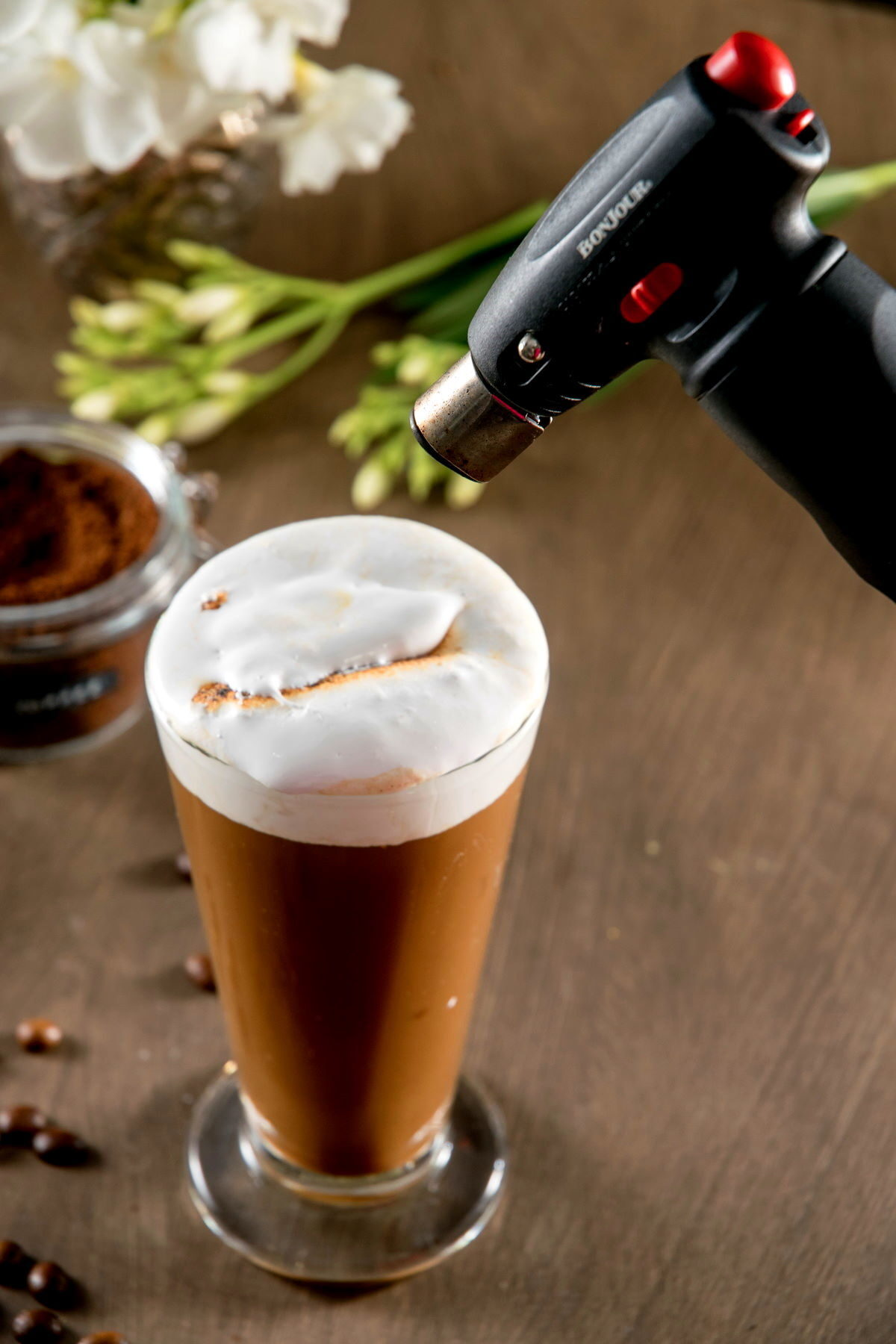 Marshmallow pumpkin latte in a clear glass mug with a kitchen torch.