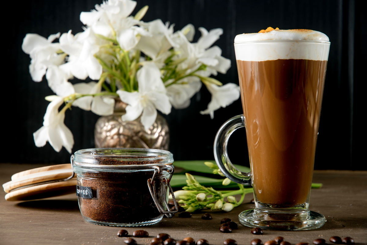 Marshmallow pumpkin latte in a mug, coffee grind on the side, white flowers in the background.