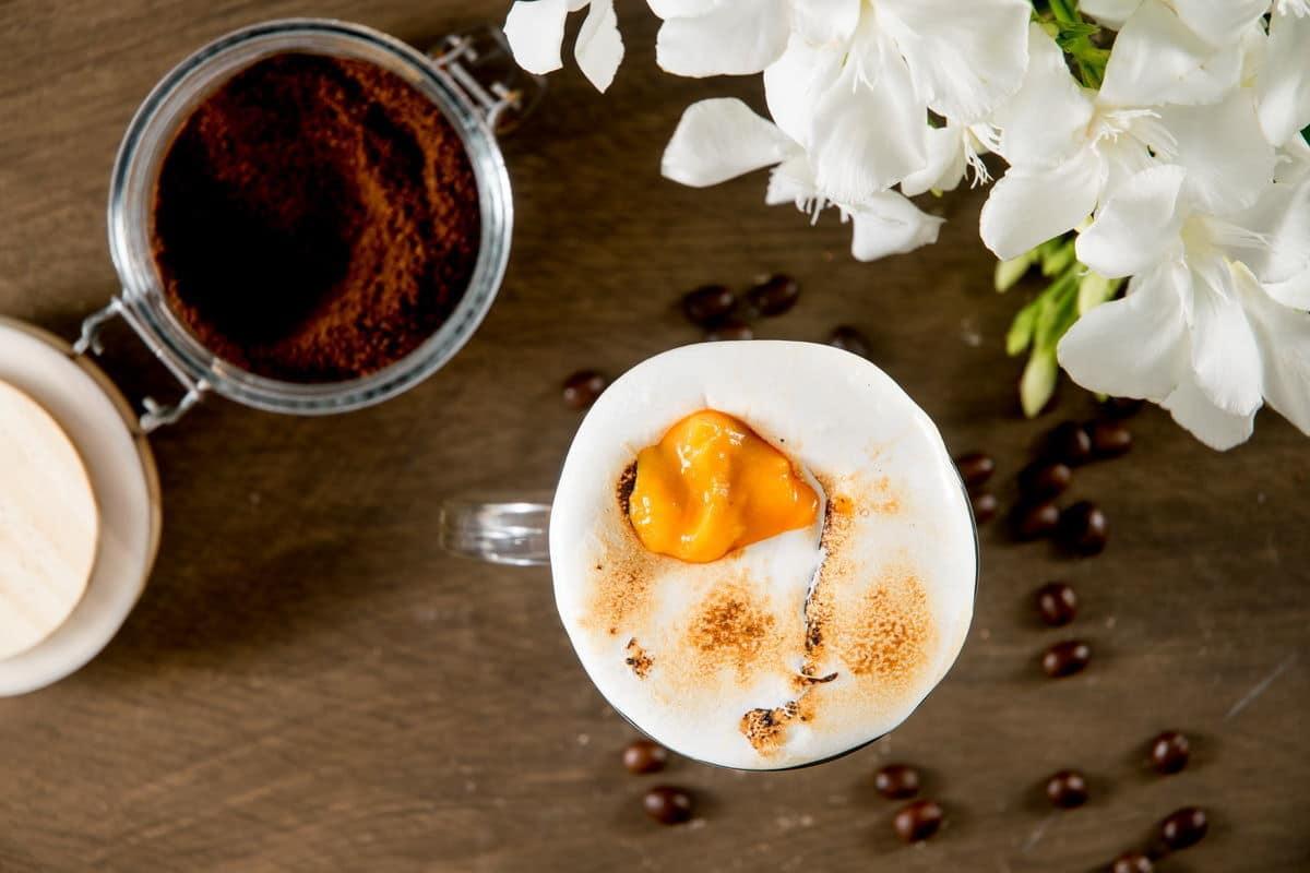 Marshmallow pumpkin latte in a mug, coffee grind on the side.