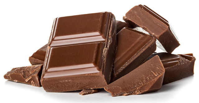 Milk chocolate pieces, white background.